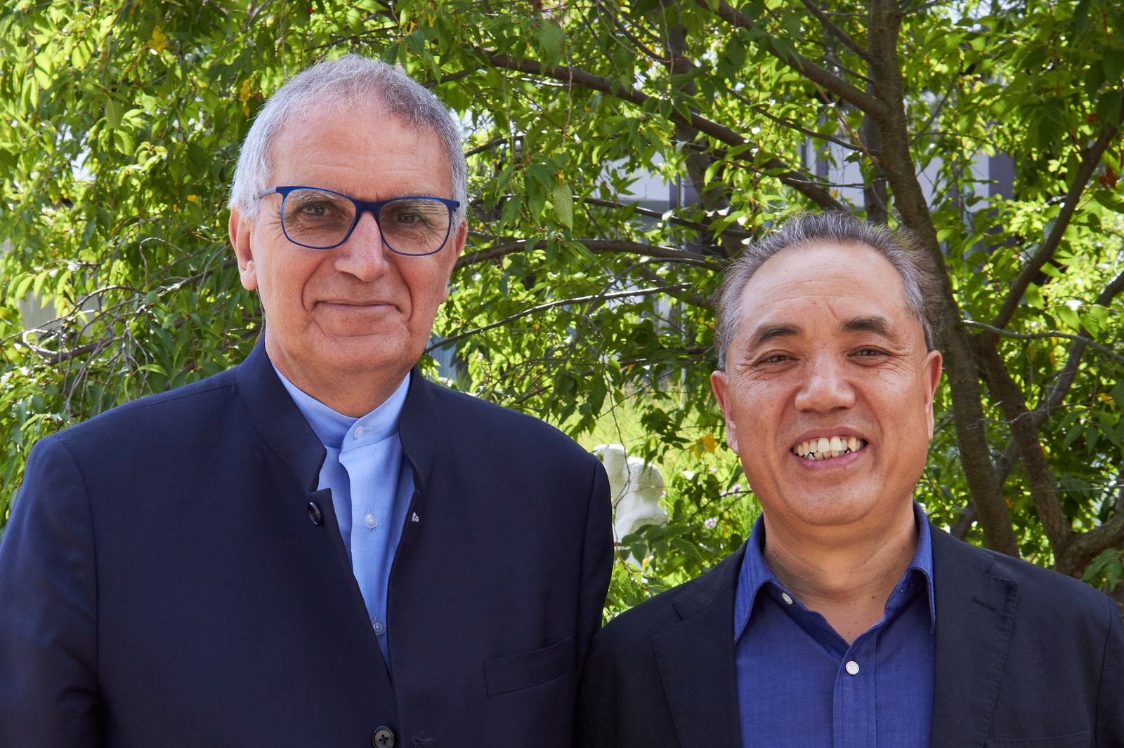 two men side by side, trees in the background